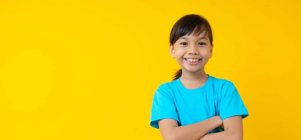 smiling-girl-yellow-background-1024x478